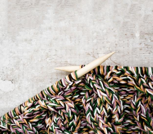Agujas de tejer e hilo sobre superficie de madera