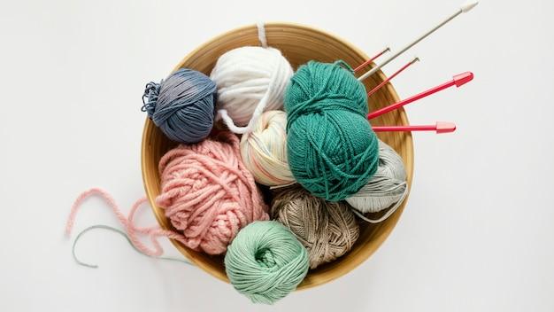 Agujas de tejer y lana en canasta