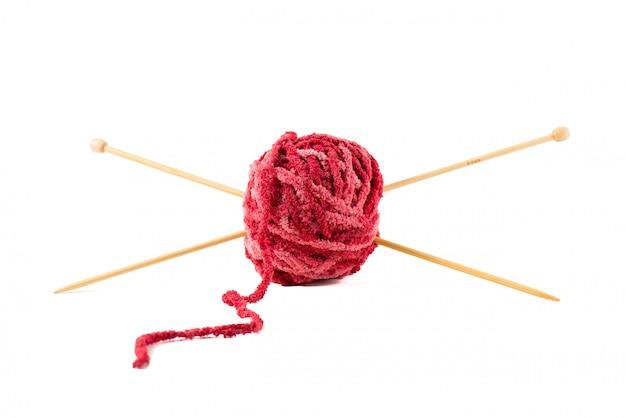 Las agujas de tejer perforan una bola de lana roja.