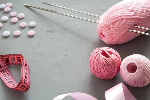 Agujas de tejer y tejer rosa sobre fondo gris