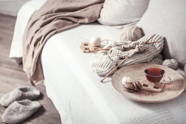 Agujas de tejer vintage e hilo con una taza de té
