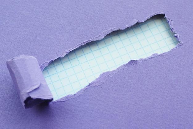 Un agujero con bordes rasgados de papel morado y papel a cuadros en el fondo. espacio para texto.