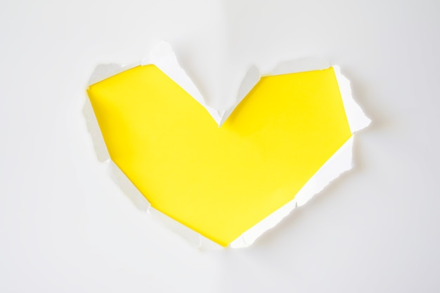 Agujero de papel amarillo con lados rasgados en forma de corazón sobre fondo blanco para espacio de copia. tarjeta de felicitación para el día de san valentín, día de la mujer o invitación de boda.