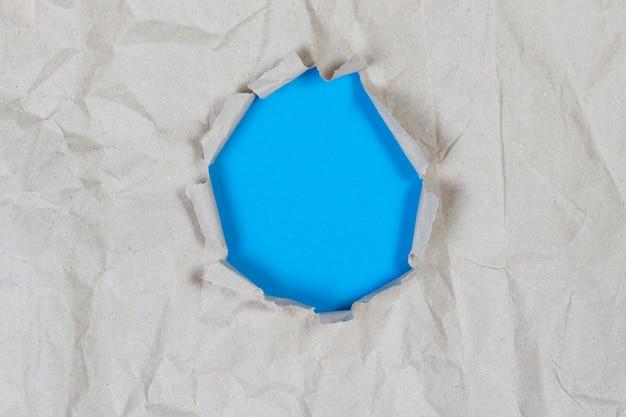 Agujero en papel arrugado viejo con fondo azul claro dentro