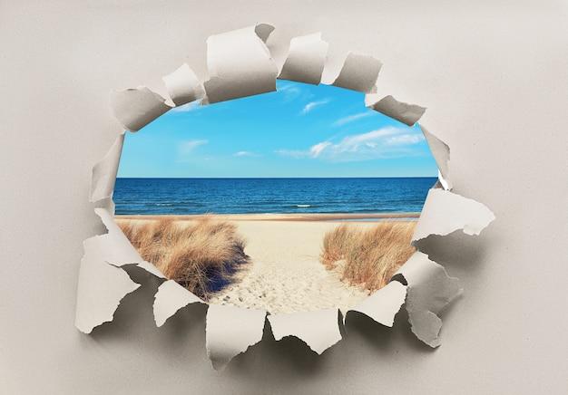 Agujero de papel con imagen de playa desierta en el mar báltico con césped en las dunas y el mar .. oferta de última hora, descuento. reapertura del norte de europa, vacaciones después de la cuarentena.