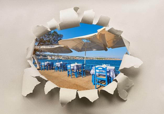 Agujero de papel con imagen de restaurante junto al mar con mesas vacías y sombrillas abiertas listas para turistas.