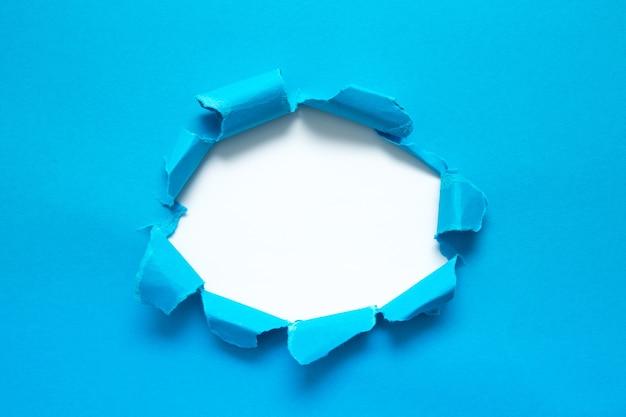 Un agujero en el papel con los lados arrancados. papel rasgado. con espacio para tu mensaje