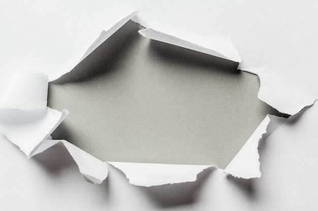 Agujero en el papel con lados rotos.