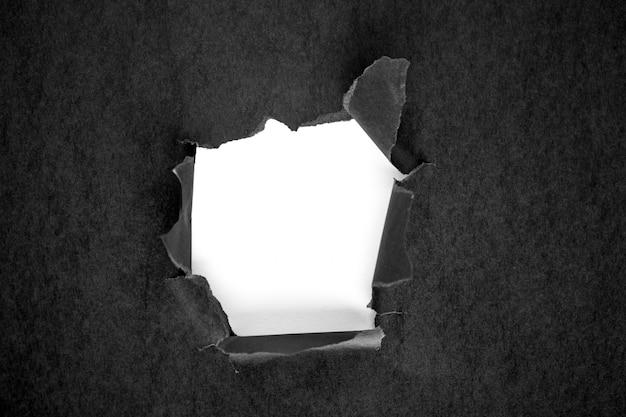 Agujero en el papel negro con lados rotos.