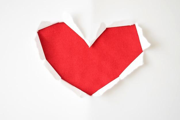 Agujero de papel rojo con lados rasgados en forma de corazón sobre fondo blanco para copiar el espacio. tarjeta de felicitación para el día de san valentín, día de la mujer o invitación de boda.