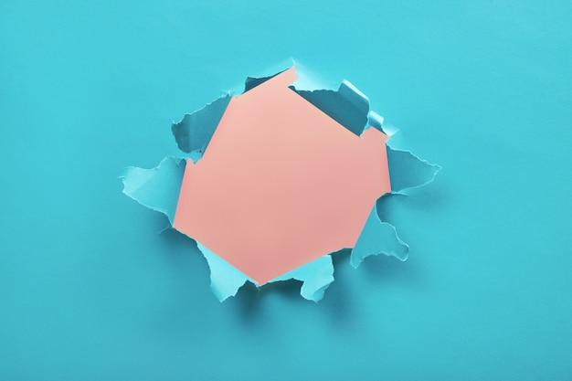 Agujero rasgado en papel azul, bordes rasgados