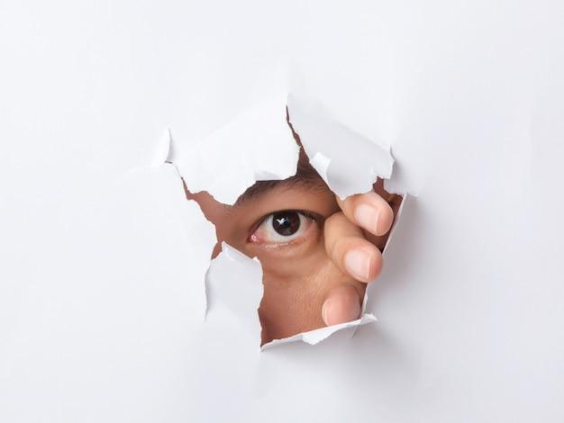 Agujero rasgado en papel con el ojo del hombre.
