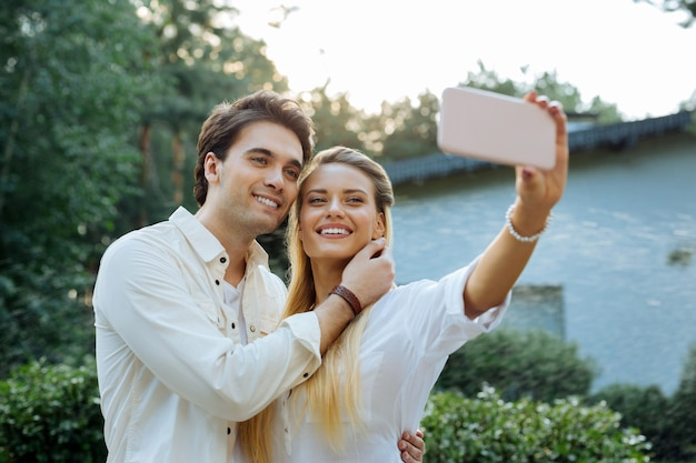 Ahora sonríe. mujer feliz alegre agujereando su smartphone mientras toma un selfie con su marido