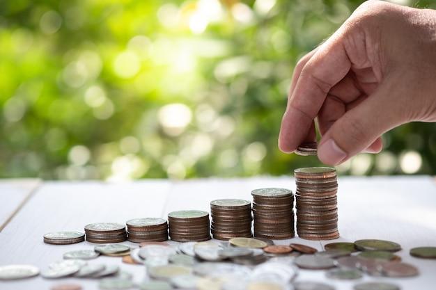 Ahorrando dinero y el concepto de inversión por mano masculina poniendo monedas de dinero apiladas para el crecimiento del negocio.