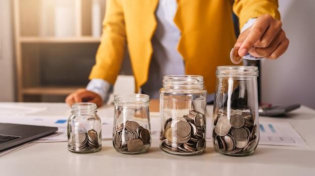Ahorrar dinero con la mano poniendo monedas en una jarra de vidrio concepto financiero