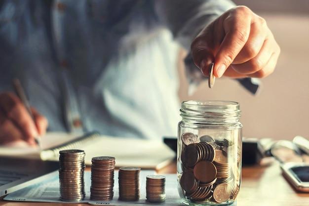 Ahorrar dinero con la mano poniendo monedas en jarra de vidrio financiero