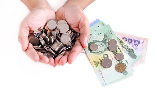 Ahorrar dinero recogiendo monedas y billetes de dinero tailandés.