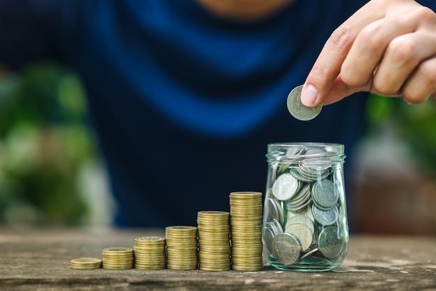 Ahorre el concepto de dinero con la mano que sostiene la moneda en la pila de monedas cada vez mayor