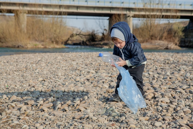 Ahorre el concepto del medio ambiente, un niño pequeño que recoge basura y botellas de plástico en la playa para tirar a la basura.