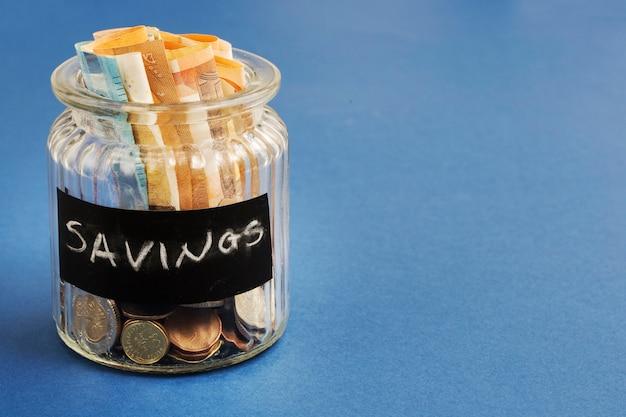 Ahorro de botella con billetes y monedas en el fondo azul