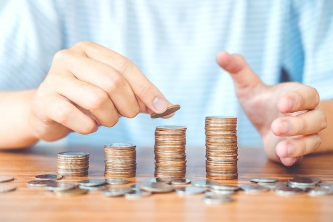 Ahorro de mano de hombre de concepto de dinero poniendo monedas finanzas de pila para presupuesto