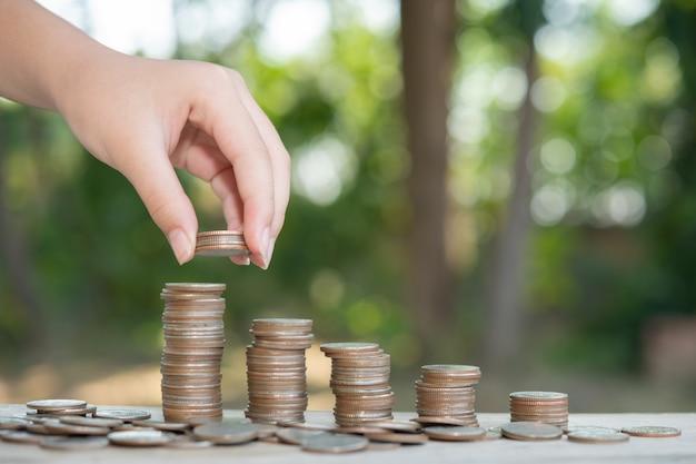 Ahorro de dinero concepto preestablecido por mano masculina poniendo dinero pila de monedas negocio en crecimiento. arregle las monedas en montones con las manos, contento con el dinero.