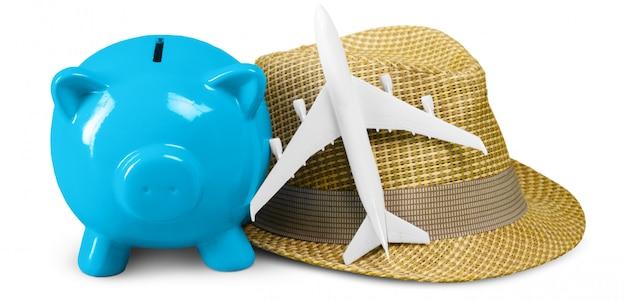 Ahorro de dinero, hucha de cerdo azul, sombrero y mini avión