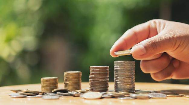 Ahorro dinero mano poniendo monedas en la pila sobre la mesa con sol. concepto de finanzas y contabilidad