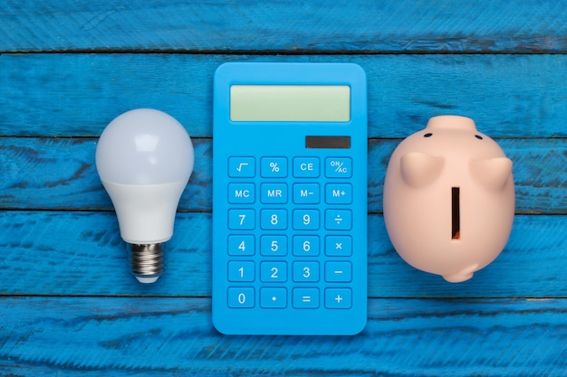 Ahorro de electricidad. bombilla de luz led y hucha, calculadora sobre superficie de madera azul. vista superior