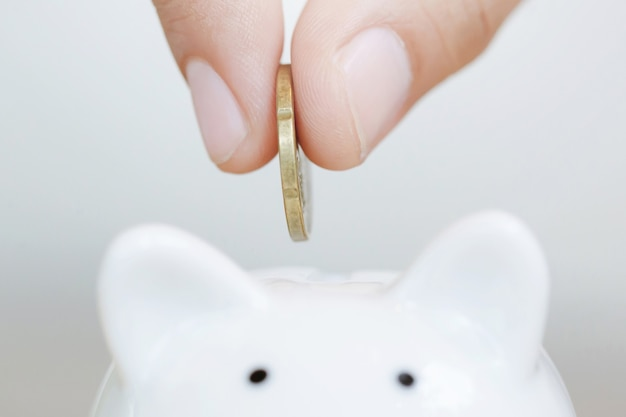 Ahorro, mano poniendo monedas de oro en la hucha blanca de la caja de dinero.
