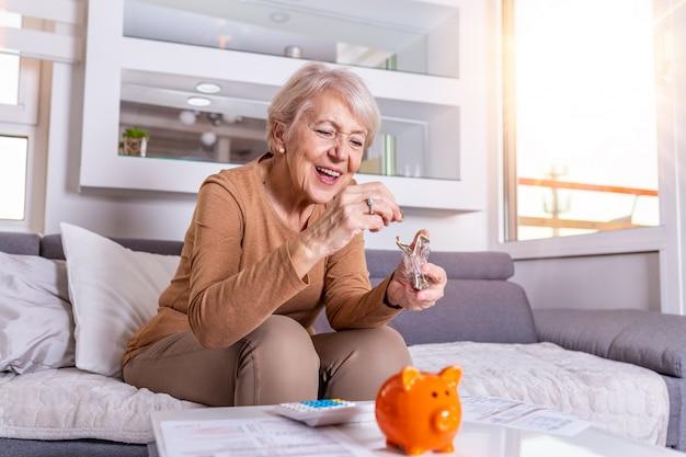 Ahorros, dinero, seguro de anualidad, jubilación y concepto de la gente - mano mayor de la mujer que pone la moneda en la batería guarra. mujer madura feliz calculando moneda en la alcancía