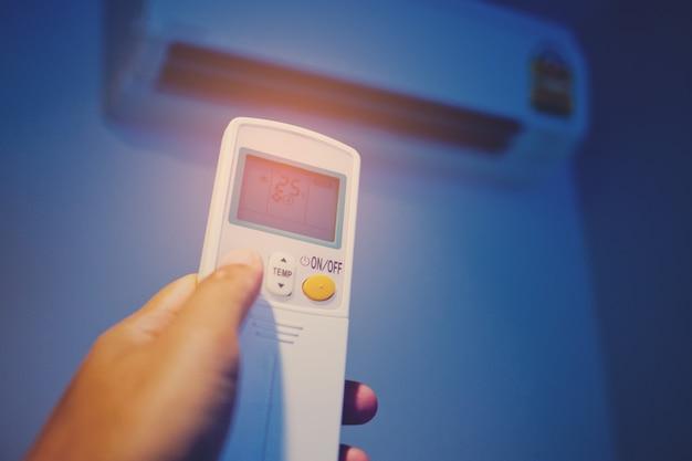 Aire acondicionado a control remoto a mano, ahorre concepto de energía