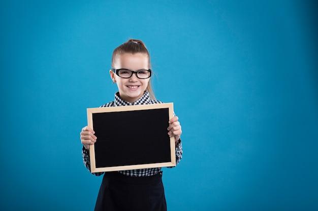 Aislado en azul, atractivo niño caucásico mantenga gran cartel vacío