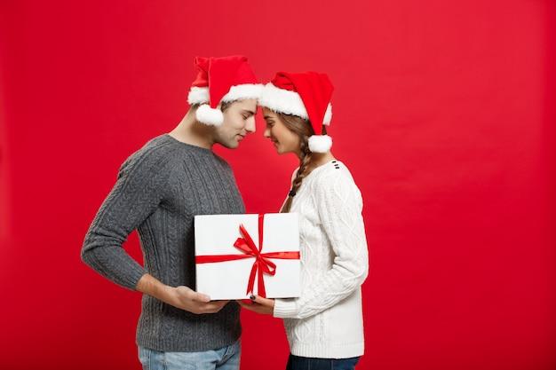 Aislado encantadora joven pareja sosteniendo firmemente con blanco regalo sobre fondo rojo.