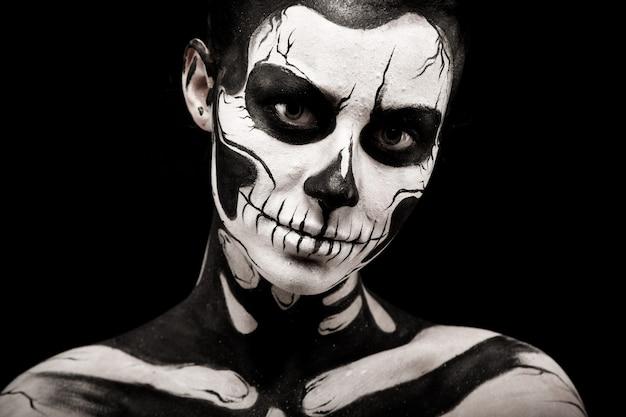 Aislado en negro, portarretrato, hermosa mujer morena caucásica joven con arte de cuerpo de scull, ojos grises, mira desde su frente