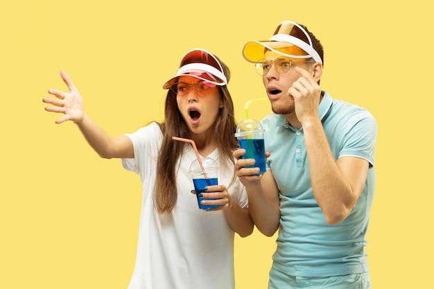 Aislado retrato de medio cuerpo de la hermosa joven pareja. mujer y hombre de pie con bebidas en gorras de colores. expresión facial, verano, concepto de fin de semana. colores de moda.