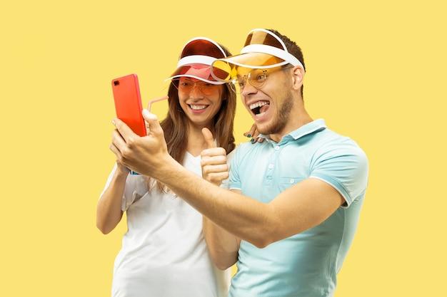 Aislado retrato de medio cuerpo de la hermosa joven pareja. mujer y hombre de pie con bebidas haciendo selfie. expresión facial, verano, concepto de fin de semana. colores de moda.