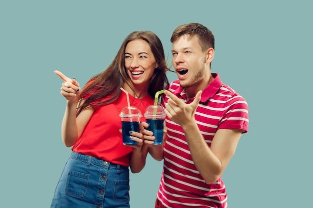 Aislado retrato de medio cuerpo de la hermosa joven pareja. mujer y hombre de pie con bebidas sonriendo y apuntando hacia arriba. expresión facial, verano, concepto de fin de semana. colores de moda.