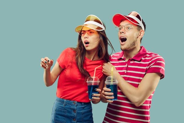 Aislado retrato de medio cuerpo de la hermosa joven pareja. sonriente mujer y hombre con gorras y gafas de sol con bebidas. expresión facial, verano, concepto de fin de semana. colores de moda.