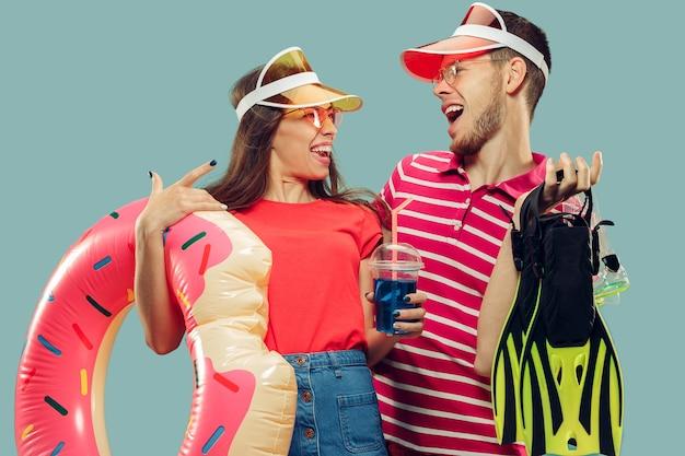 Aislado retrato de medio cuerpo de la hermosa joven pareja. sonriente mujer y hombre con gorras y gafas de sol con equipo de natación. expresión facial, verano, concepto de fin de semana.