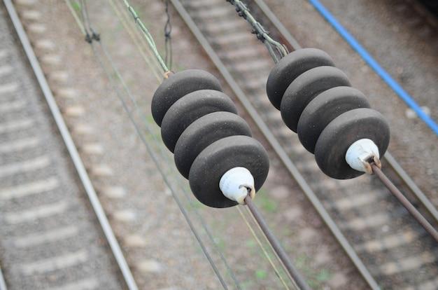 Aisladores eléctricos en los cables de contacto en el fondo de una vía férrea borrosa. foto macro con enfoque selectivo