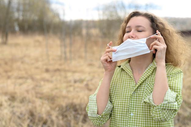 El aislamiento final y el concepto de cuarentena del virus corona covid-19. joven europea se quitó una máscara médica de la cara y respira aire fresco en la naturaleza al aire libre