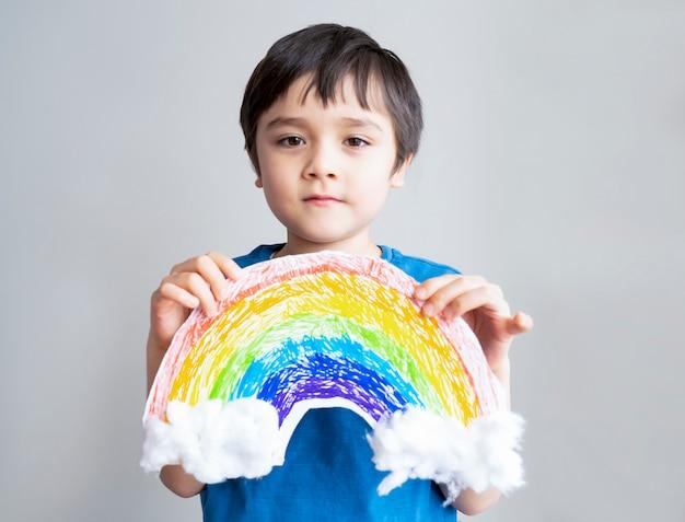 Aislamiento del niño del retrato que lleva a cabo la imagen del dibujo del arco iris en el pape blanco.