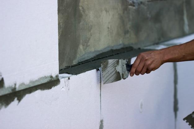 Aislamiento de paredes con paneles de poliestireno, aplicación e instalación de cola.