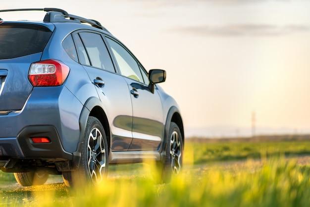 Ajardine con el coche azul del camino en el camino de la grava. viajar en automóvil, aventura en la vida silvestre, expedición o viajes extremos en un automóvil suv.
