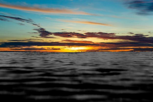 Ajardine el fondo del cielo de la puesta del sol sobre el mar negro.