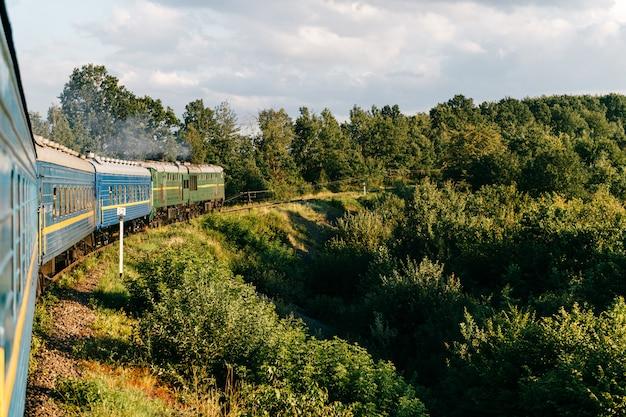 Ajardine la hermosa vista fuera de la ventana de montar el tren entre la naturaleza del verano con las colinas, las montañas y el bosque.
