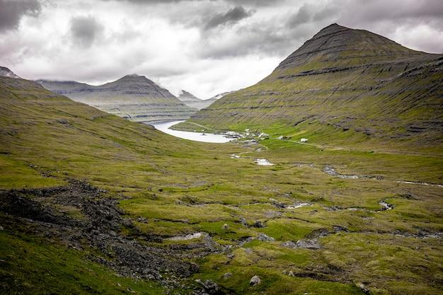 Ajardine la naturaleza en las islas feroe, pueblo cerca de un lago.