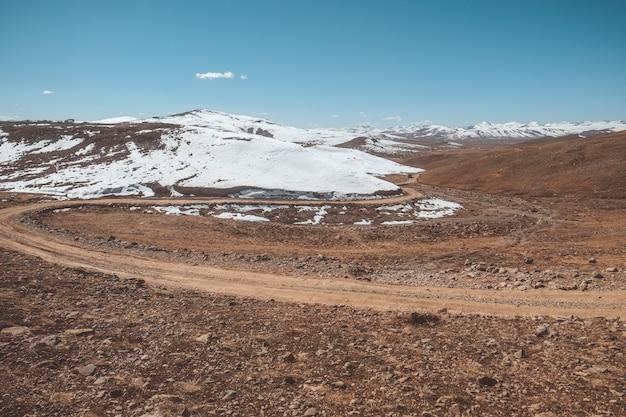 Ajardine la vista de un camino de tierra de la bobina a lo largo de la cordillera capsulada nieve, paquistán.