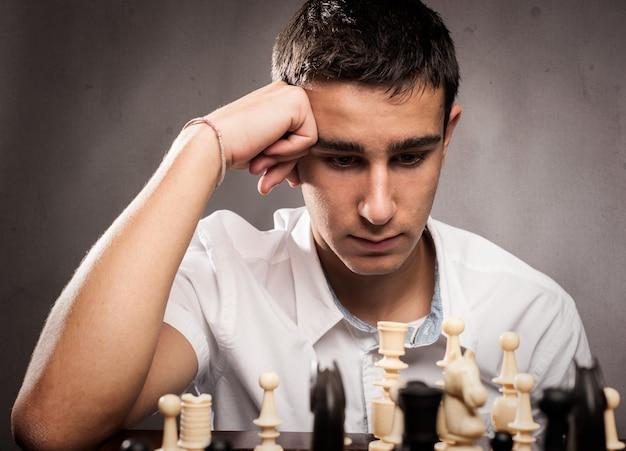 Ajedrez boyplaying concentrado sobre un fondo gris